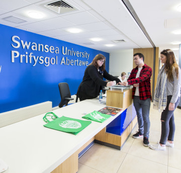 People chatting at Swansea University's reception area.