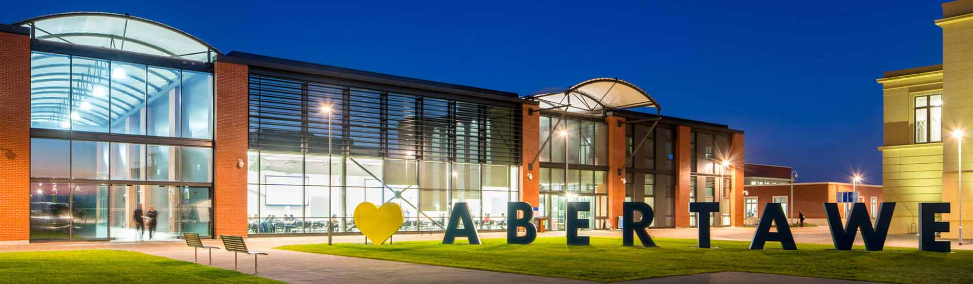 This image was taken at night time. The College of Engineering is lit up. There is a large sign outside which reads 'I love Abertawe'. Abertawe is Welsh for 'Swansea.