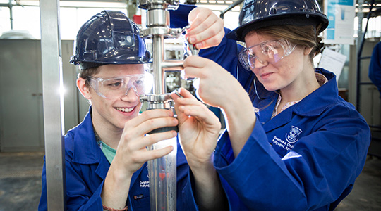 One male and one female student operating a mechanical instrument. They are wearing blue overalls, blue hard hats and protective glasses.
