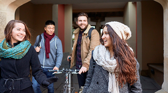 Four students walking through the grounds of Singleton Park Campus. There are two females who are smiling at each other. There are two males in the background, one of them is pushing a bike.