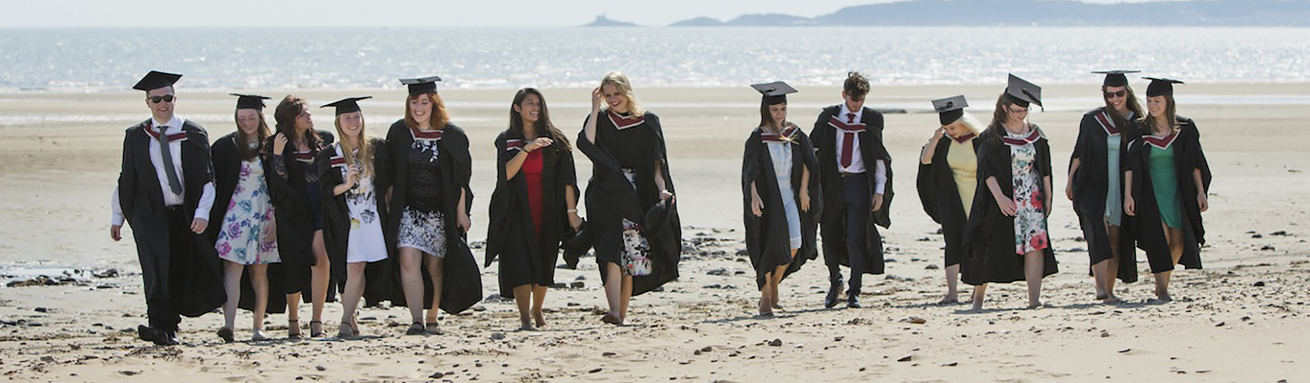 Group of graduates on the beach by the Bay Campus