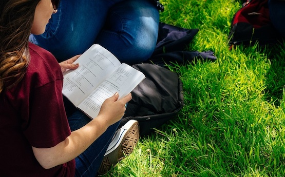 Student reading a book whist sitting on the grass