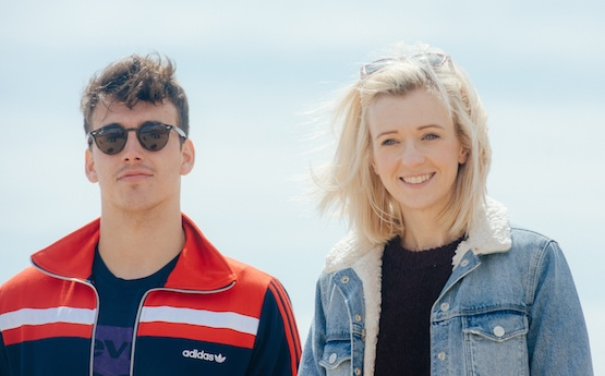 Two students walking on the beach in Swansea