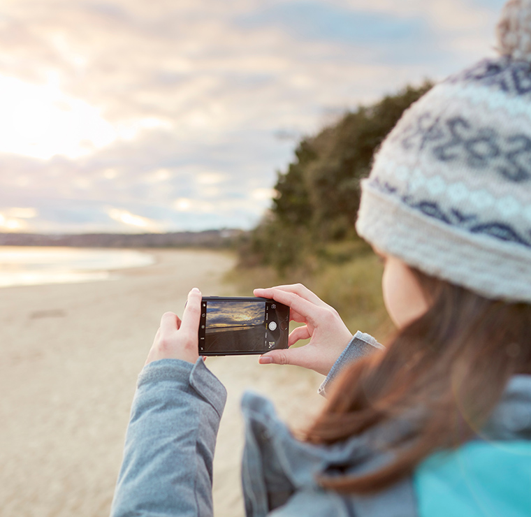 Image of student taking a picture of the beach