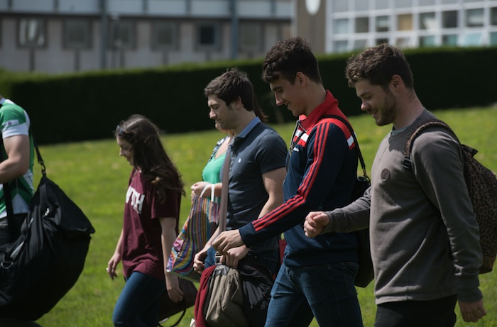 Group of students walking on the green by the Abbey on the Singelton Campus