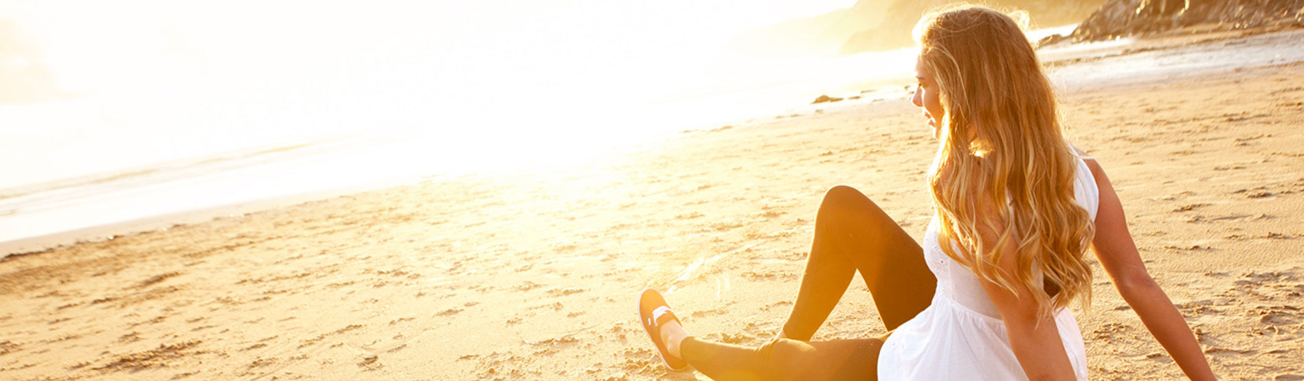 Female student sat on beach at sunset