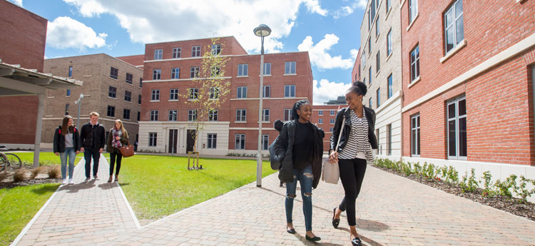 Exterior view of Bay Campus Residences in the sunlight with students walking through