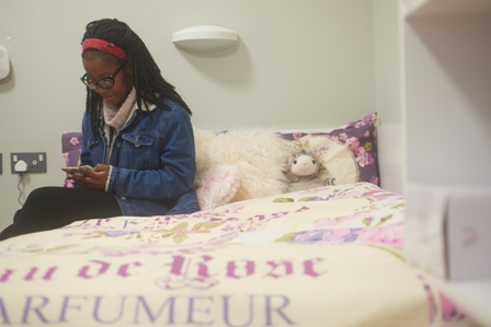 A female student sitting on her double bed in her student room and looking at her phone