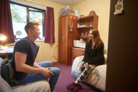Female and male student sitting in a student room, chatting and smiling