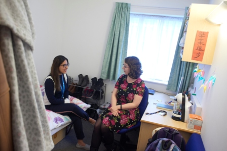 Two female students sitting in a student room, chatting and smiling