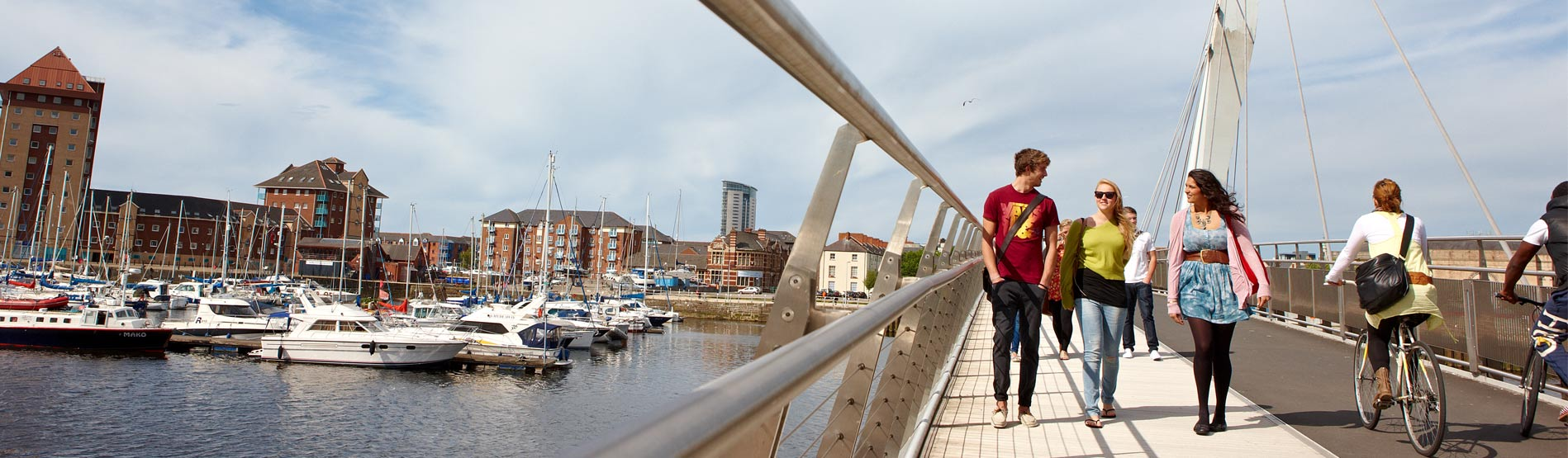 People walking over the bridge in SA1, Swansea with the Marina in the Background