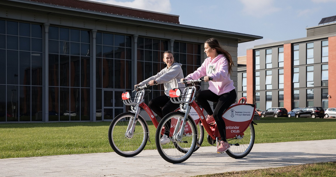 2 female students riding bikes on the Bay campus