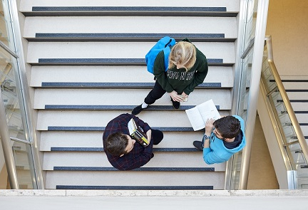Three students standing on the stairs