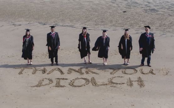 students standing over a thank you message in the sand at graduation