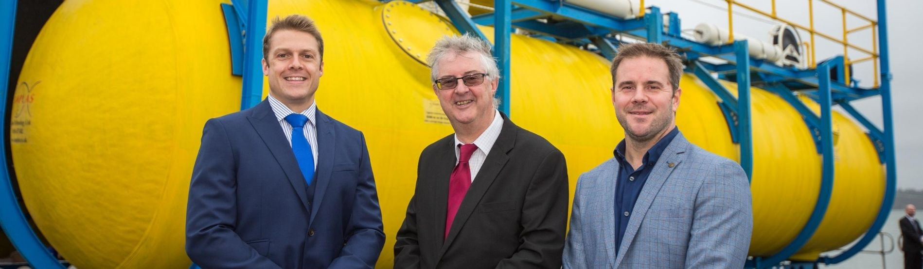 Dr Gareth Stockman, Mark Drakeford (First Minister of Wales) and Dr Graham Foster standing in front of the Wave Sub.