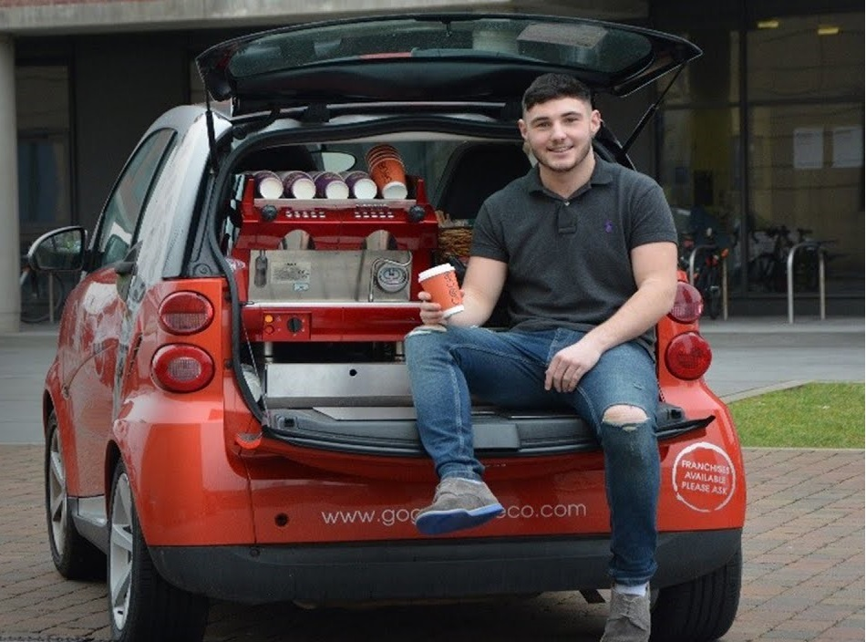 Boy sitting in a car boot with coffee machine