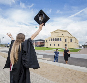 girl at grad with arms in air