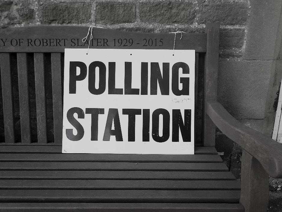 'Polling Station' card on a wooden bench.