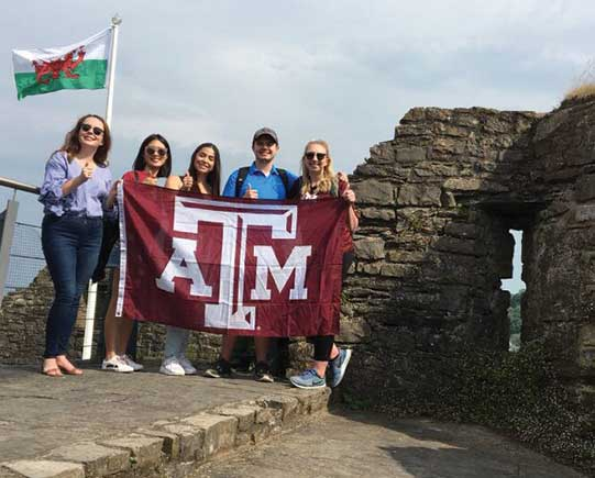 ATM University students in Ostyermouth Castle, Welsh Flag in background.