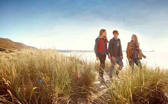 Three students walking through sand dunes on warm clothes at dusk