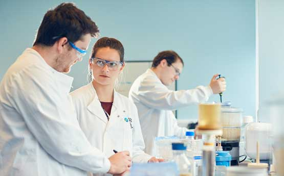 A Man in a white lab coat speaking to a women in a white lab coat around some lab equipment.