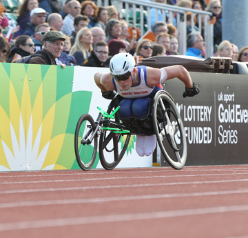 Man in wheelchair racing on athletics track