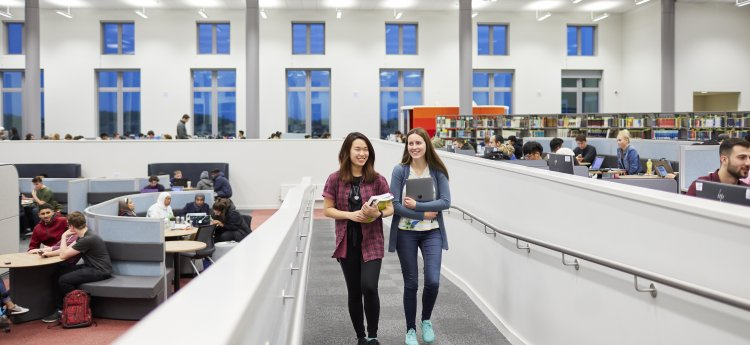 two students carrying books walking in the Bay Library