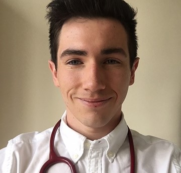 A head and shoulders photo of Alex Ruddy with a stethoscope around his neck