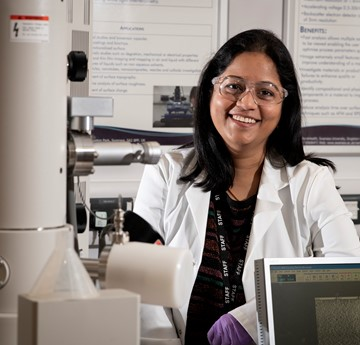 Photo of Anitha Devadoss in a lab, wearing goggles and a lab coat