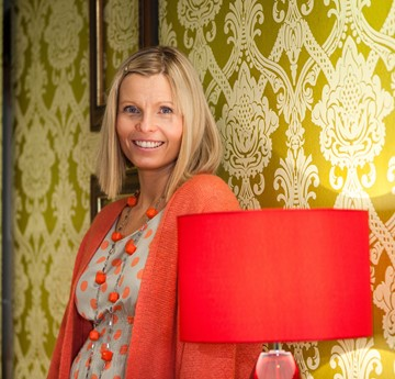 Image of Nia Parry in a room with yellow and white ornate wallpaper and a red lamp