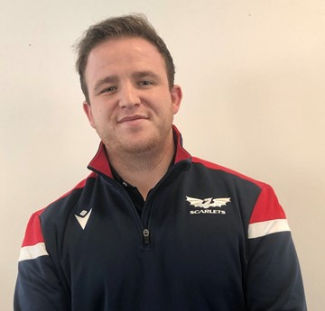 A head and shoulders photo of Sam Cook wearing a Scarlets rugby jacket.