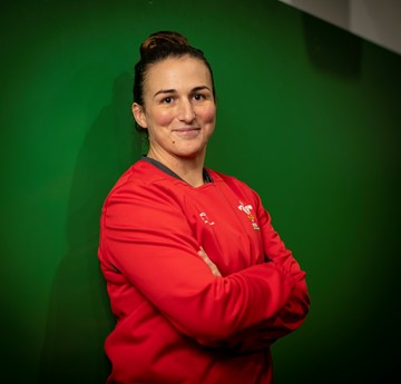 Siwan Lillicrap in her Wales rugby kit standing in front of a green screen with her arms folded.