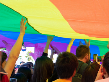 Students holding up a large piece of rainbow fabric
