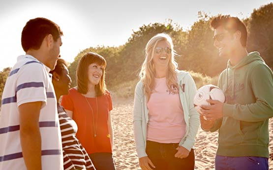 Students smiling, laughing stood on the Beach in the sun