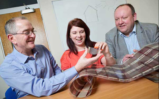 Three people looking at a new material created through research and development