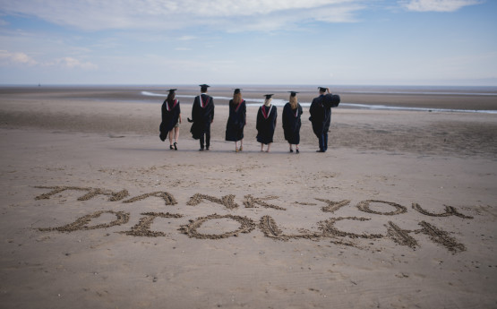 graduates in cap and gowns, walking on the beach with the words Thank you/Diolch written in the sand