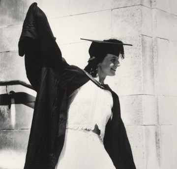 Black and white photo of a female student graduating. She holds her right arm in the air above her head as she smiles at someone off camera.