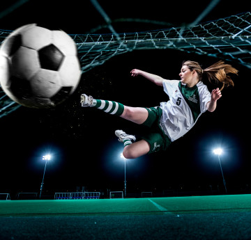 Women's footballer kicking ball towards camera