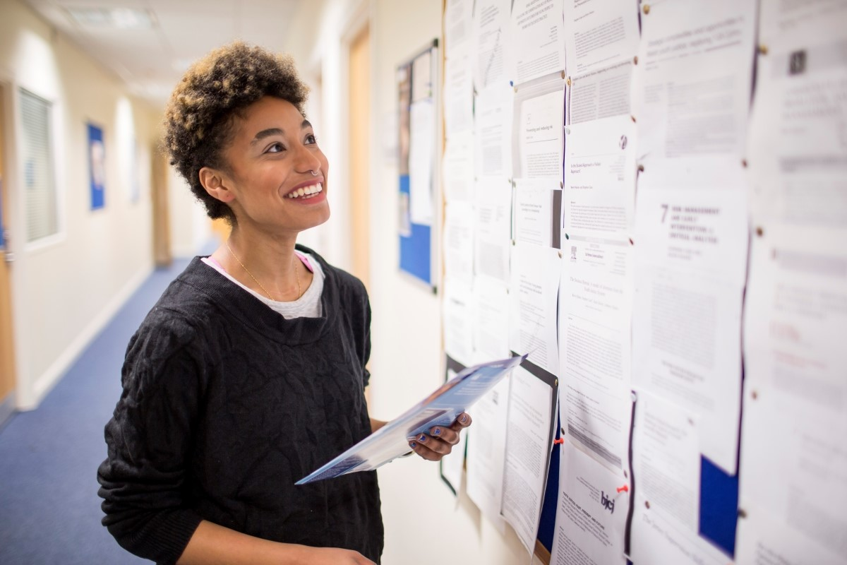 Female student smiling and looking at noticeboard