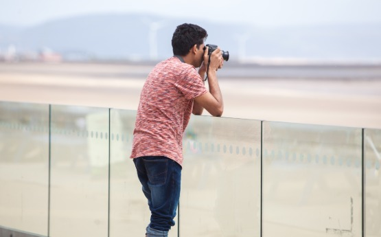 Male student leaning on glass wall outside 360 and taking a photograph with a camera