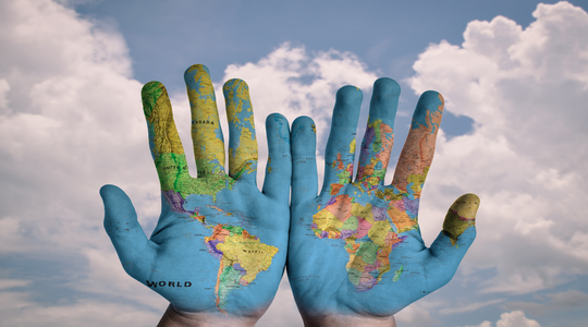World map painted across two hands. Blue sky in the background.