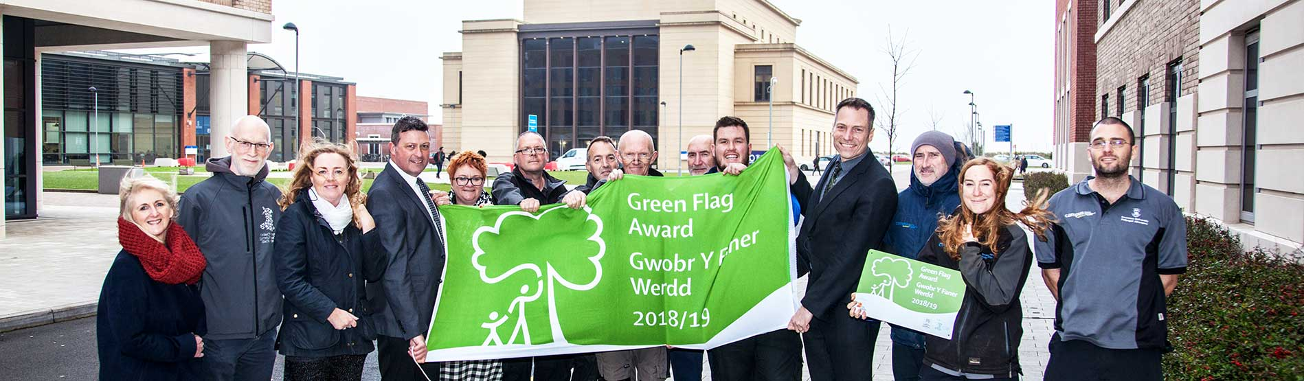 Grounds team members flying the Green Flag at the Bay Campus