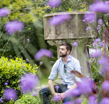 A male student sitting in the grounds of Singleton Abbey - purple flowers are in bloom