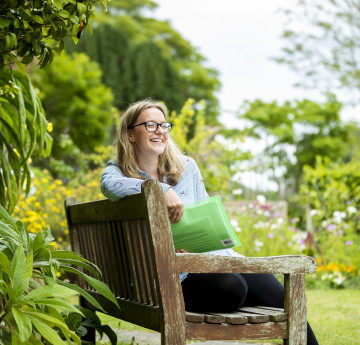 A female wearing a light blue top sits on a bench in the grounds of Singleton Abbey.