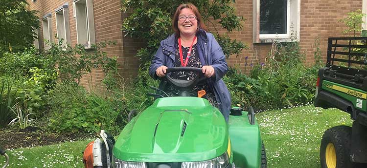 A female staff member learning to drive a grounds lawnmower during a volunteer day