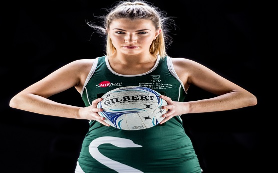 A Swansea University netball player posing for a photo holding the ball.