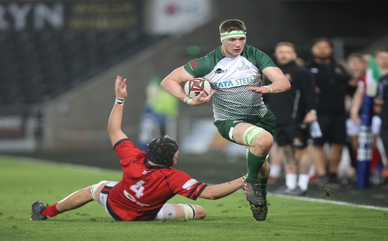 A Men's rugby player running away from the opposition.