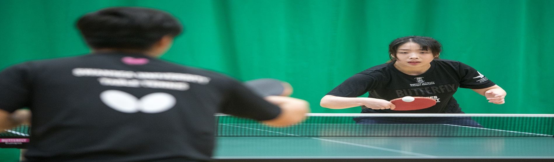 Two table tennis players exchanging a rally