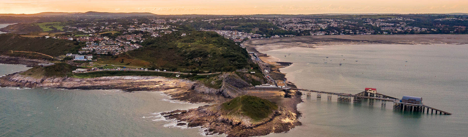 an aerial shot of mumbles head and the pier at sunset