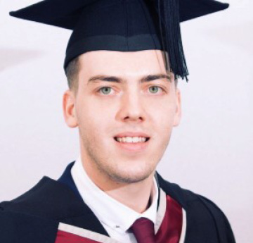 male smiling in graduation cap and gown